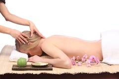 Ciérrese para arriba de las manos que dan masajes a la frente de una mujer hermosa en el balneario de la belleza Foto de archivo