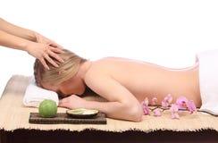 Ciérrese para arriba de las manos que dan masajes a la frente de una mujer hermosa en el balneario de la belleza Fotos de archivo