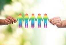 Ciérrese para arriba de las manos que detienen a la gente gay de cadena de papel Fotos de archivo