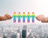 Ciérrese para arriba de las manos que detienen a la gente gay de cadena de papel Foto de archivo