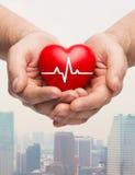 Ciérrese para arriba de las manos que llevan a cabo el corazón con el cardiograma Imagen de archivo