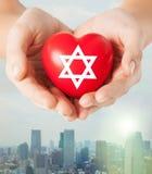 Ciérrese para arriba de las manos que llevan a cabo el corazón con la estrella judía Imagenes de archivo