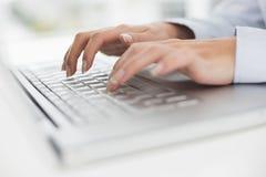 Ciérrese para arriba de las manos que mecanografían en el teclado del ordenador portátil Foto de archivo libre de regalías
