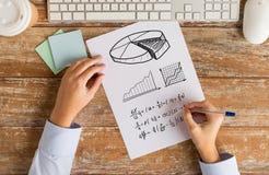 Ciérrese para arriba de las manos que solucionan tarea o que escriben la ecuación Fotografía de archivo libre de regalías