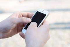 Ciérrese para arriba de las manos que sostienen el teléfono con la pantalla en blanco Fotografía de archivo libre de regalías