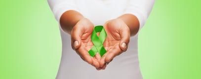 Ciérrese para arriba de las manos que sostienen la cinta verde de la conciencia Foto de archivo