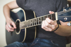 Ciérrese para arriba de las manos que tocan la guitarra foto de archivo libre de regalías