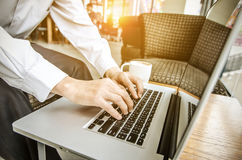 Ciérrese para arriba de las manos de un hombre que mecanografían en un ordenador portátil en una cafetería imagenes de archivo