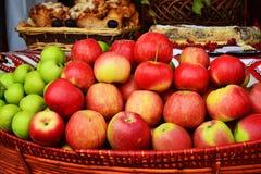 Ciérrese para arriba de las manzanas verdes apiladas en una cesta imagen de archivo