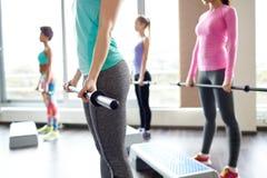Ciérrese para arriba de las mujeres que ejercitan con las barras en gimnasio Imágenes de archivo libres de regalías