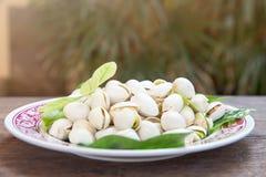 Ciérrese para arriba de las nueces de pistachos en la tabla de madera Pistacho en de madera foto de archivo