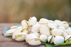 Ciérrese para arriba de las nueces de pistachos en la tabla de madera Pistacho en de madera fotos de archivo