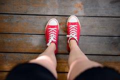 Ciérrese para arriba de las piernas de la muchacha en keds rojos Desde arriba de Fotografía de archivo