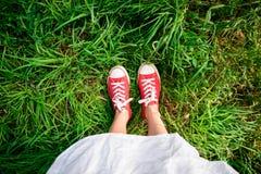 Ciérrese para arriba de las piernas de la muchacha en keds rojos en hierba Imágenes de archivo libres de regalías