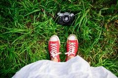 Ciérrese para arriba de las piernas de la muchacha en keds rojos en hierba Fotografía de archivo
