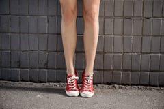 Ciérrese para arriba de las piernas de la muchacha en keds sobre la pared gris Imágenes de archivo libres de regalías