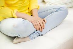 Ciérrese para arriba de las piernas de la mujer joven que se sientan en el sofá casero Foto de archivo libre de regalías