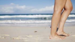Ciérrese para arriba de las piernas de la mujer que caminan en la playa metrajes