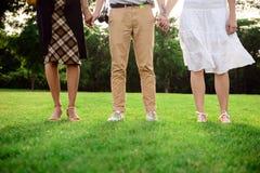 Ciérrese para arriba de las piernas del ` de los amigos en keds en hierba Imágenes de archivo libres de regalías