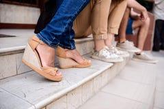 Ciérrese para arriba de las piernas del ` de los amigos en los keds que se sientan en la escalera Foto de archivo