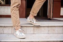 Ciérrese para arriba de las piernas del hombre en los keds que van abajo de las escaleras Imagen de archivo