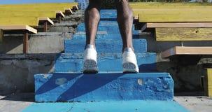 Ciérrese para arriba de las piernas del hombre negro que funcionan con para arriba las escaleras en el estadio almacen de metraje de vídeo