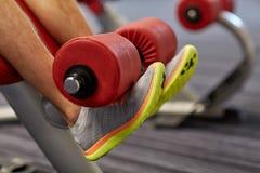 Ciérrese para arriba de las piernas del hombre que ejercitan en la máquina del gimnasio Foto de archivo libre de regalías