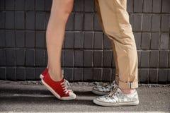 Ciérrese para arriba de las piernas del par en keds sobre la pared gris Imagen de archivo libre de regalías