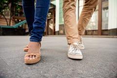 Ciérrese para arriba de las piernas del par en los keds que caminan abajo de la calle Fotos de archivo libres de regalías