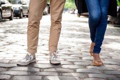 Ciérrese para arriba de las piernas del par en los keds que se colocan en la calle Fotos de archivo