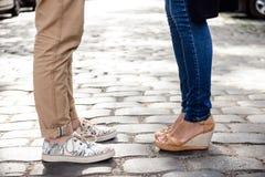 Ciérrese para arriba de las piernas del par en los keds que se colocan en la calle Foto de archivo libre de regalías