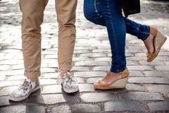Ciérrese para arriba de las piernas del par en los keds que se colocan en la calle Imagenes de archivo