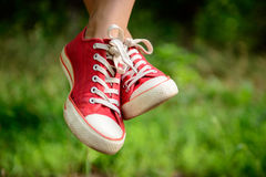 Ciérrese para arriba de las piernas del ` s de la muchacha en keds rojos en hierba Foto de archivo