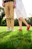 Ciérrese para arriba de las piernas del ` s de los pares en keds en hierba Imagenes de archivo