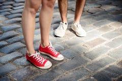 Ciérrese para arriba de las piernas del ` s de los pares en los keds que se colocan en la calle Foto de archivo
