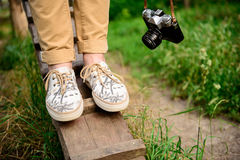 Ciérrese para arriba de las piernas del ` s del hombre en los keds que se colocan en el escritorio Fotografía de archivo libre de regalías