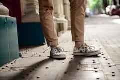 Ciérrese para arriba de las piernas del ` s del hombre en los keds que se colocan en la calle Foto de archivo libre de regalías