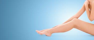 Ciérrese para arriba de las piernas desnudas de la mujer sobre fondo azul foto de archivo