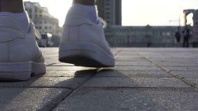Ciérrese para arriba de las piernas masculinas que se mueven en las zapatillas de deporte blancas, anuncio del calzado del deport almacen de video