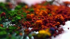 Ciérrese para arriba de las tintas secas de diverso color, concepto del arte Fondo con la naranja, verde brillantes, iridiscentes metrajes