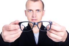 Ciérrese para arriba de lentes en las manos masculinas aisladas en blanco Foto de archivo