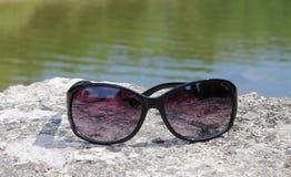 Ciérrese para arriba de lentes de sol negros con las lentes púrpuras en roca con agua adentro detrás imagen de archivo libre de regalías