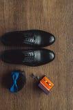 Ciérrese para arriba de los accesorios del hombre moderno Bowtie azul, zapatos de cuero, correa, mancuernas y anillos de bodas en Imagen de archivo libre de regalías