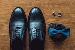 Ciérrese para arriba de los accesorios del hombre moderno Bowtie azul, zapatos de cuero, correa y mancuernas Fotos de archivo libres de regalías