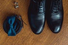 Ciérrese para arriba de los accesorios del hombre moderno Bowtie azul, zapatos de cuero, correa y mancuernas Imágenes de archivo libres de regalías