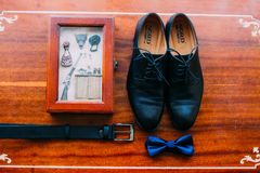 Ciérrese para arriba de los accesorios del hombre moderno Bowtie azul, zapatos de cuero, correa y postal en el fondo rústico de m Foto de archivo