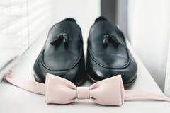 Ciérrese para arriba de los accesorios del hombre moderno corbata de lazo beige, zapatos de cuero negros Imágenes de archivo libres de regalías