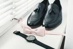Ciérrese para arriba de los accesorios del hombre moderno corbata de lazo beige, zapatos de cuero negros, correa y reloj Foto de archivo