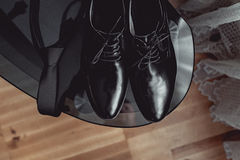 Ciérrese para arriba de los accesorios del hombre moderno corbata negra y zapatos de cuero en la tabla de cristal negra Imagenes de archivo