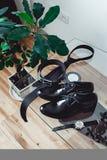 Ciérrese para arriba de los accesorios modernos del novio la corbata negra, los zapatos de cuero ceñe y mira Fotografía de archivo libre de regalías